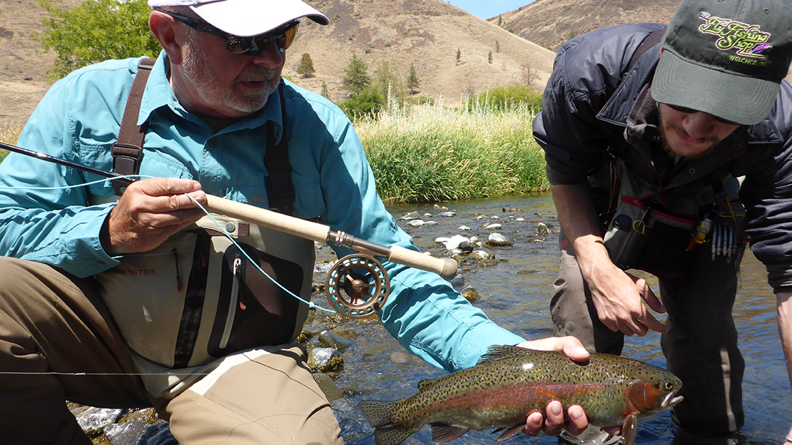 Fly fishing instructors, Mark Bachmann and Frank Day examine a nice rainbow trout caught while Spey fishing the Deschutes River in Oregon.
