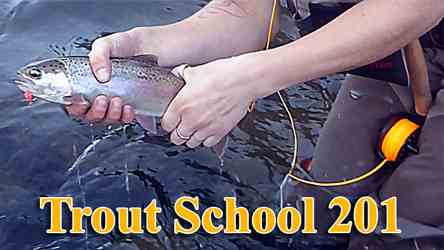 Two day fly fishing trout school; learn to catch trout on a fly. This is a picture of a young woman holding a trout.