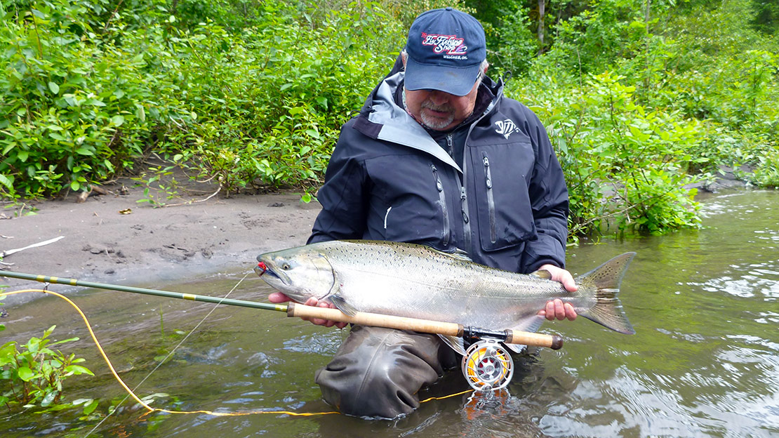 Mark Bachmann examines a Spring Chinook caught with a Hatch Finatic reel on the Sandy River in Oregon.